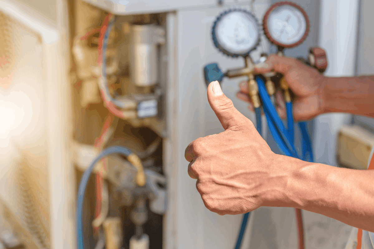 man showing thumbs up while checking the air conditioner